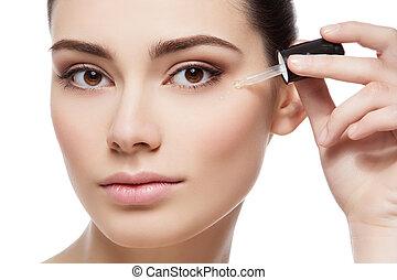 Girl applying eye serum - Beautiful young woman applying...