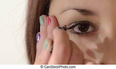girl applying eyeliner