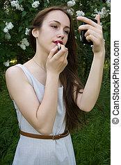 Girl applying lipstick on the lips