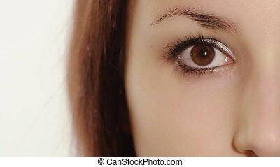 girl applying mascara - A young woman doing her makeup,...