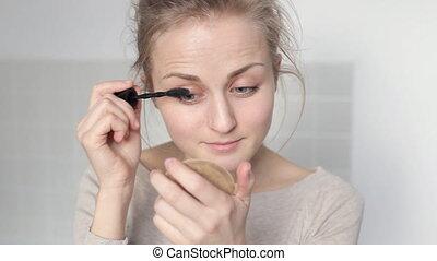 Girl applying mascara - Young woman doing makeup at home....