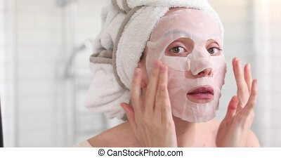 Girl applying mask on her face looking in mirror - Woman...