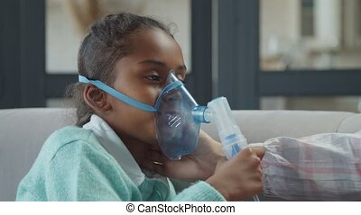Portrait of sick cute african american preadolescent girl applying medicine inhalation treatment using ultrasonic wave nebulizer at home, inhaling medicine for asthma while mom gently caressing her.