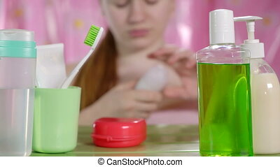 Girl applying roll-on deodorant to her armpit in bathroom view through the toiletries