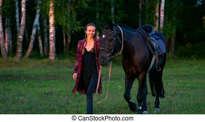 girl approaches camera leading horse under bridle