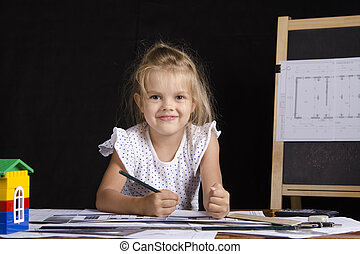 Girl-architect sitting behind a Des
