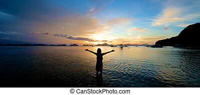 Girl with arms wide open in El Nido in the Philippines.