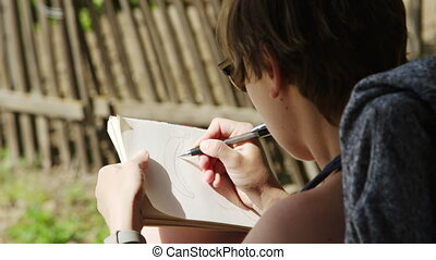 Girl artist in sunglasses draws sketches in notebook - Back...