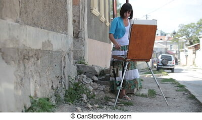 Girl artist painting picture on the street