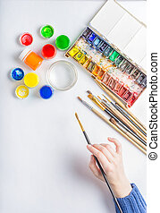Girl artist paints with colored inks on a white background paper. Multicolored watercolor, gouache, palette and brushes. A brush in the hands of a woman.