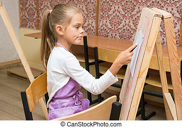 Girl artist with a smile look in the picture on the drawing lesson