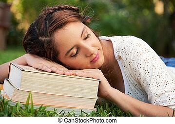 girl asleep on top of books