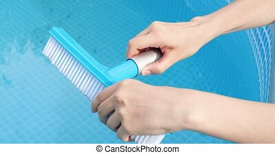 girl assembling swimming pool brush, cleaning pool with a special brush.