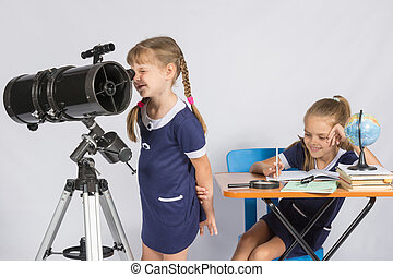 Girl astronomer looks through the eyepiece of the telescope, and the other girl sitting happily at the table