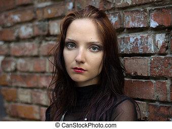 Girl at a brick wall