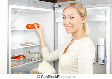 Girl at a refrigerator - A smiling blonde takes a tomato ...