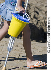 Girl at beach - Young girl on crutches with sand pails at...