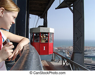 girl waiting at a station of the aerial passenger line above the port of barcelona, spain (transbordador aeri)
