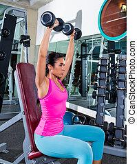 girl at gym seated dumbbell shoulder press