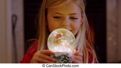 Front view close up of a young Caucasian girl holding a snow globe in the sitting room at Christmas time, looking at it and smiling