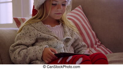 Front view close up of a young Caucasian girl wearing a Santa hat sitting on the sofa using a tablet computer in her sitting room at Christmas time