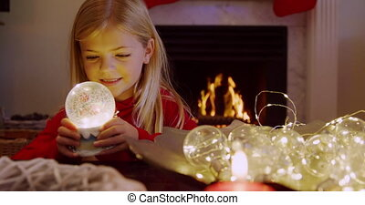 Front view of a young Caucasian girl holding a snow globe in the sitting room at Christmas time, smiling, with an open fire burning in the fireplace behind her