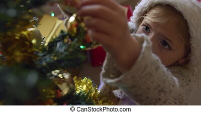 High angle view of a smiling young Caucasian girl wearing a Santa hat decorating the Christmas tree in her sitting room, reaching up to hang a bauble