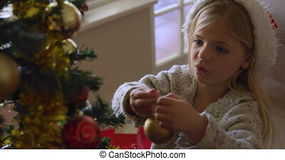 High angle view of a smiling young Caucasian girl wearing a Santa hat decorating the Christmas tree in her sitting room