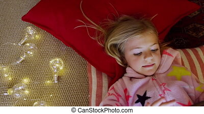 Overhead view of a happy young Caucasian girl lying on cushions on the floor wearing a onesie using a tablet in her sitting room at Christmas time, with lit fairy lights beside her