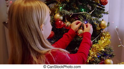Rear view close up of a young Caucasian girl decorating the Christmas tree in her sitting room at Christmas time