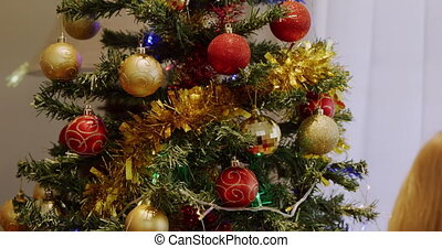 Rear view of a young Caucasian girl decorating the Christmas tree in her sitting room with baubles at Christmas time