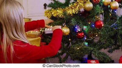 Rear view of a young Caucasian girl decorating the Christmas tree in her sitting room with fairy lights at Christmas time
