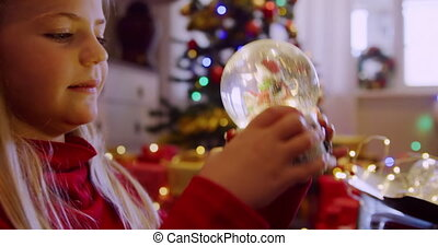 Side view close up of a young Caucasian girl holding and shaking a snow globe in the sitting room at Christmas time and looking at it, a decorated Christmas tree in the background
