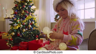 Side view of a happy young Caucasian girl wearing a Santa hat and a onesie playing with fairy lights in her sitting room at Christmas time
