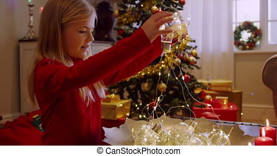 Side view of a smiling young Caucasian girl holding fairy lights in the sitting room at Christmas time and looking at them, a decorated Christmas tree in the background