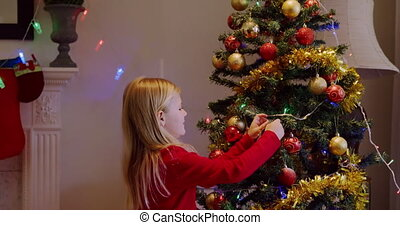 Side view of a young Caucasian girl decorating the Christmas tree in her sitting room at Christmas time. She is smiling.