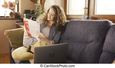 Girl at home sitting on couch holding notebook, studying. -...