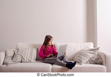 Girl at home sitting on sofa, playing with laptop - Little...