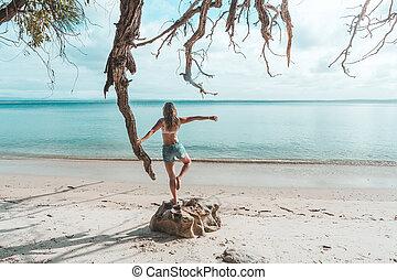 Girl at idyllic beach in early morning, balance, fitness, freedom