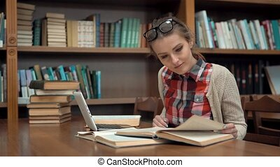 Girl at Library Table - Smiling caucasian girl studying in...
