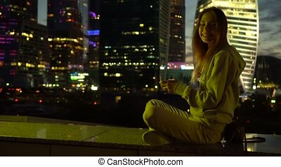 Girl at night with a smartphone on the Internet on a...