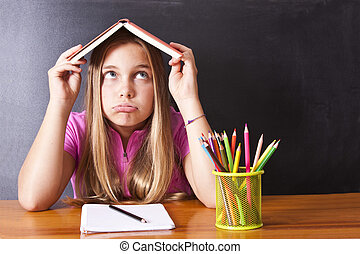 girl at school with book on head stressed