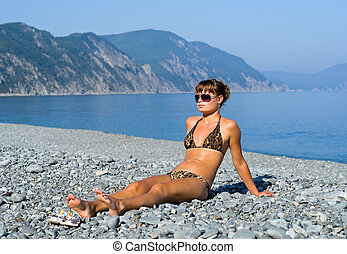 A girl sunburns on seabeach with grey-blue pebbles. On background are seawater and capes.