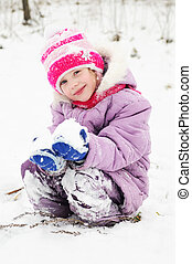 girl at snowy winter outdoors - little happy girl playing at...