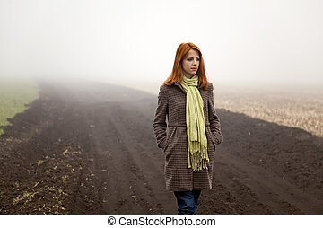 Girl at spring field in fog time.