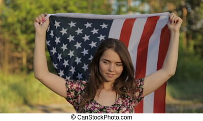 Girl at sunset with American flag in hands