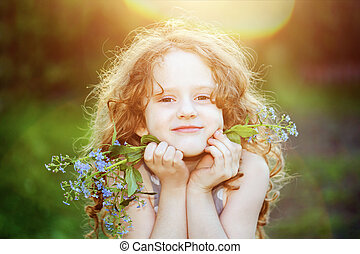 Girl at sunset with blue flowers in her hands. Background...