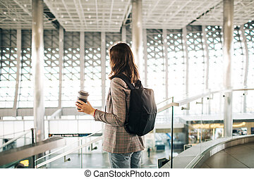 Girl at the airport from the back, with coffee cup.