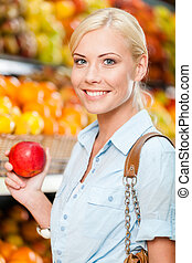Girl at the market choosing fruits hands apple