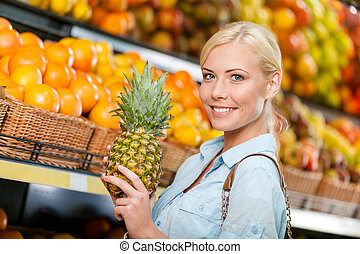 Girl at the market choosing fruits hands pineapple
